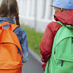 two students from behind wearing backpacks
