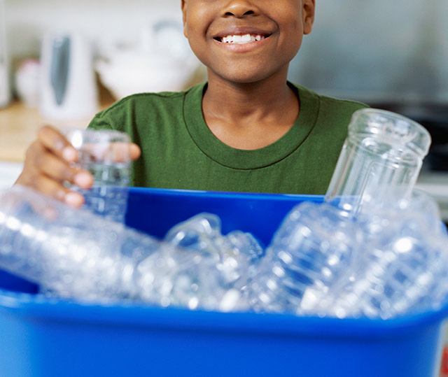 child placing plastic bottle in recycle bin